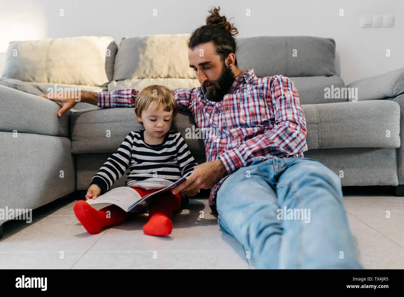 Padre e hija sentado en el piso en el salón leyendo un libro juntos Foto de stock