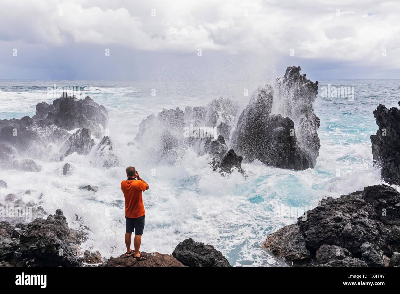 Ee.Uu., Hawai, Isla Grande, Laupahoehoe Beach Park,hombre tomando fotos de Rompiendo olas en la costa rocosa Foto de stock