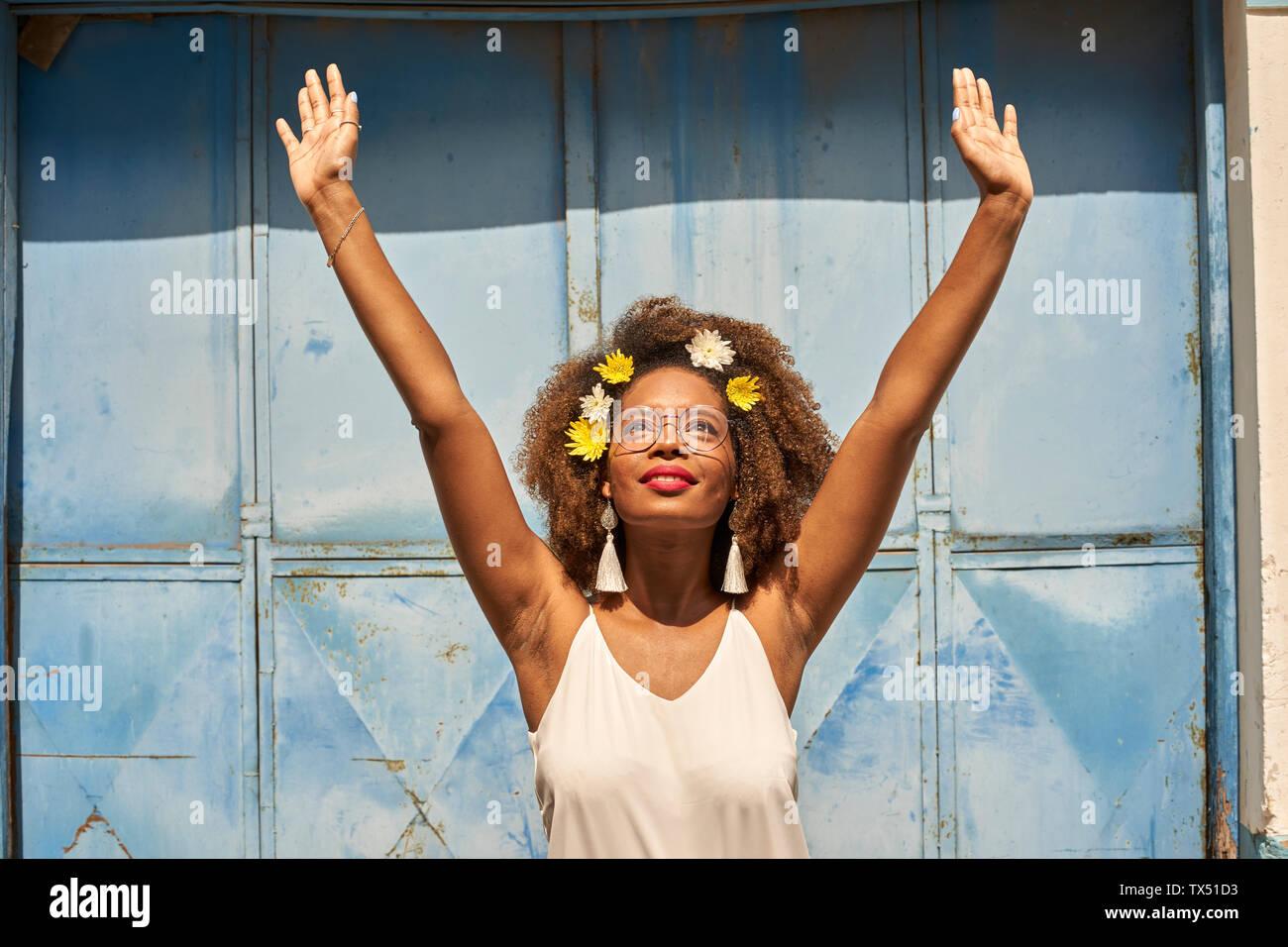 Retrato de mujer joven feliz con labios rojos con gafas y flores en su cabello Foto de stock