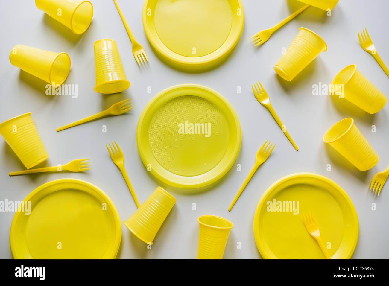 Single use utensilios de picnic amarillo sobre gris. Medio ambiente, ecológico, descartar la basura plástica para reciclar el concepto.vista desde arriba. Sentar planas. Patrón. Foto de stock