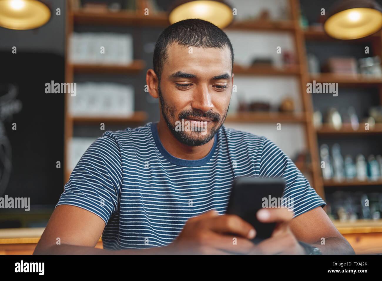 Joven con smartphone en café Foto de stock