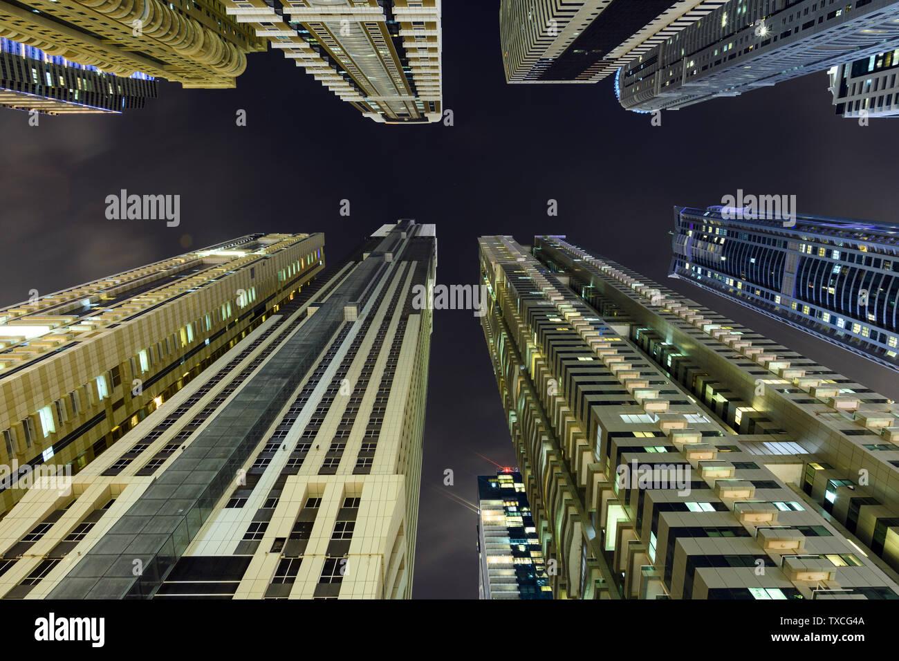 (Perspectiva Diferente) impresionante vista desde la parte inferior hasta la parte superior de algunos rascacielos y torres iluminados durante la noche en la zona de Dubai Marina. Foto de stock