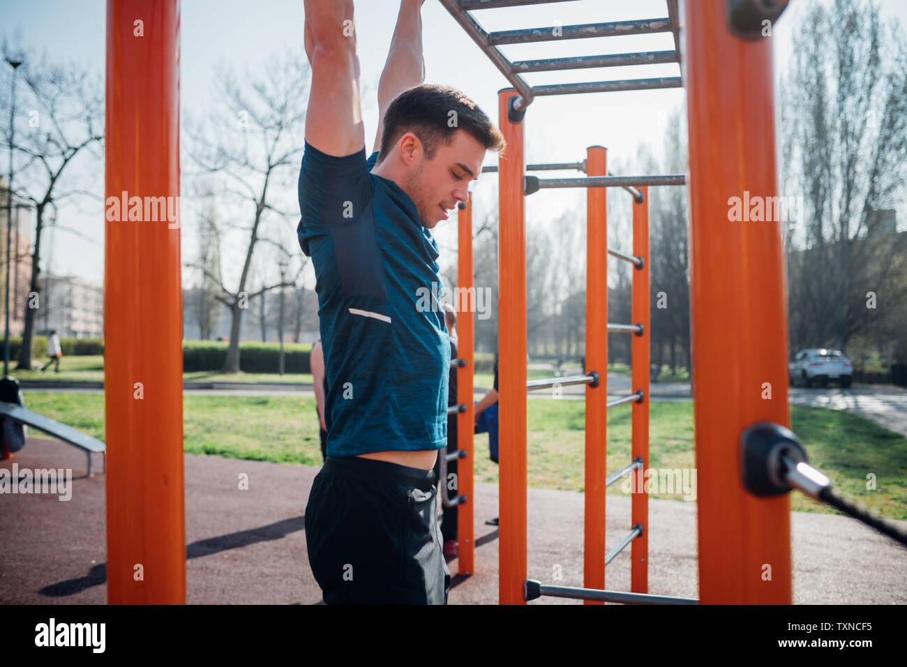 Calistenia en el gimnasio exterior, joven colgando de equipamiento de ejercicio Imagen De Stock