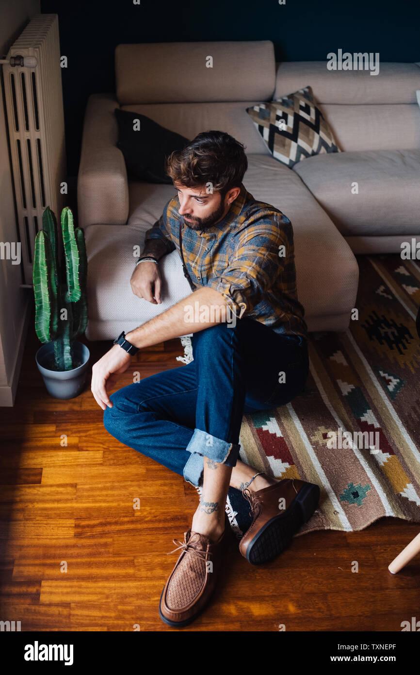 Mitad hombre adulto sentado en el suelo del cuarto de estar mirando a través de la ventana Foto de stock