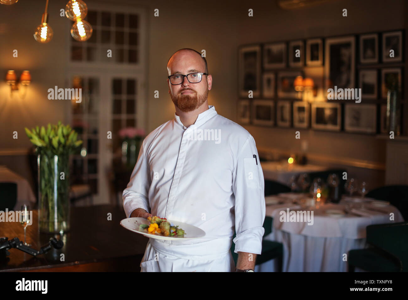 Chef con Exótico plato de ensalada de hojas y flores en restaurante. Foto de stock