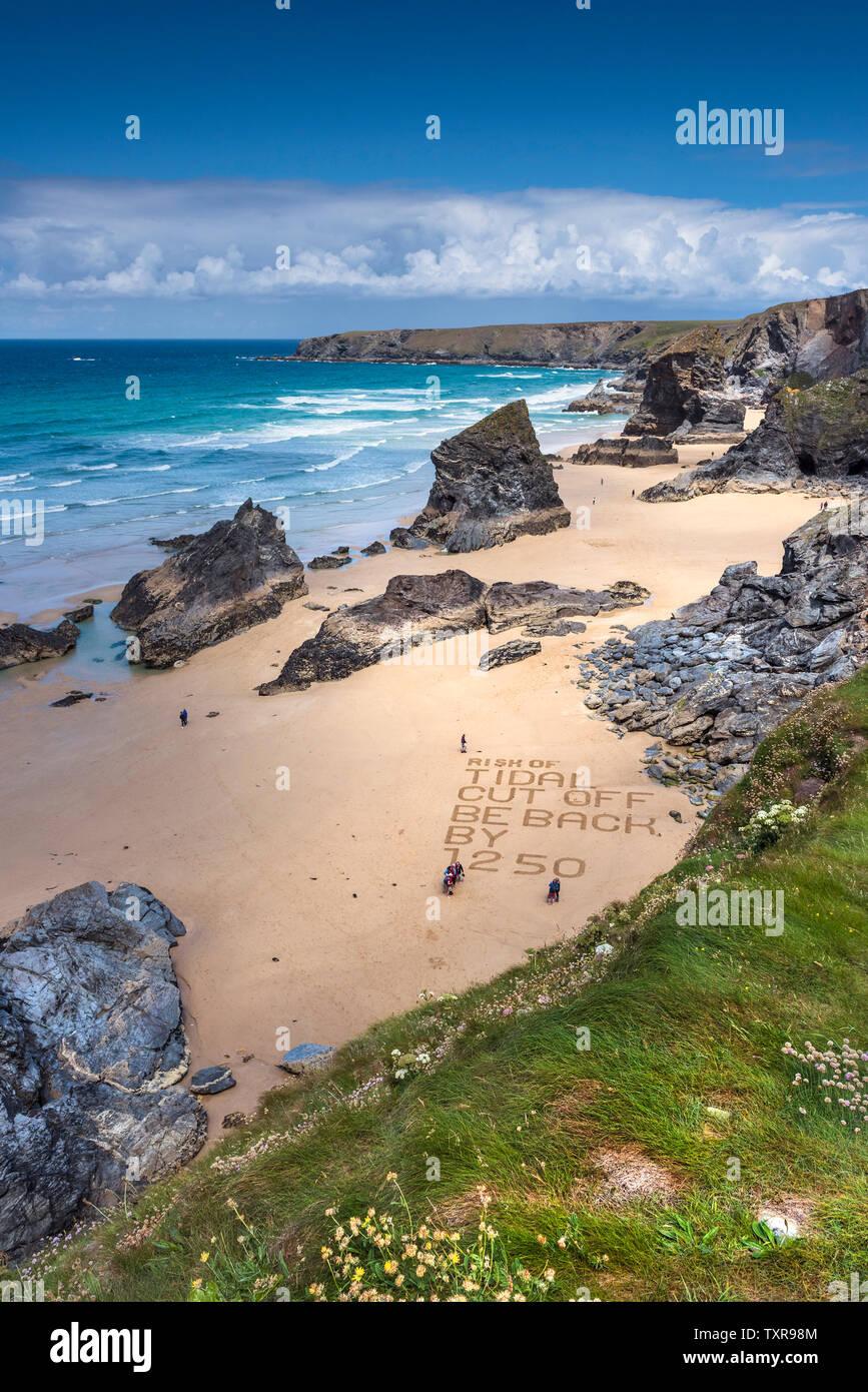 Un mensaje de advertencia escrito en la arena de la playa en el robusto Bedruthan espectaculares pasos en el norte de la costa de Cornwall. Foto de stock