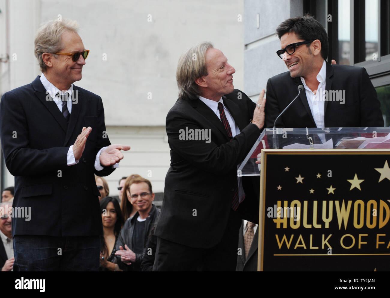 """Gerry Beckley (L) y Dewey Bunnell (C), los miembros del grupo de rock clásico y ganador de un premio Grammy, """"el dúo América, reaccionar a las observaciones formuladas por el actor John Stamos (R) durante una ceremonia en honor a ellos con el 2,459th estrella en el Paseo de la Fama de Hollywood en Los Angeles el 6 de febrero de 2012. UPI/Jim Ruymen Imagen De Stock"""