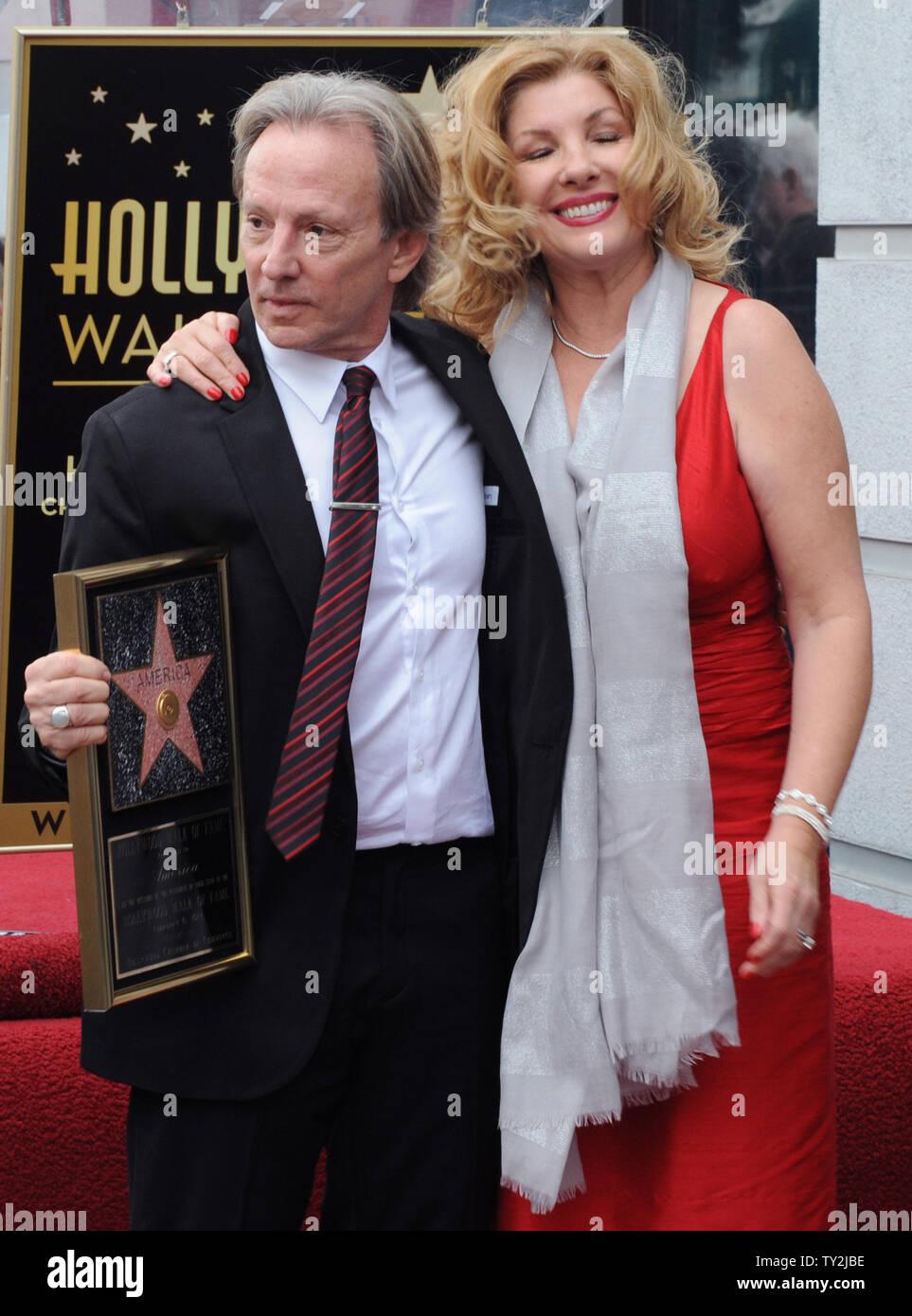 """Dewey Bunnell (L) miembro del grupo de rock clásico y ganador de un premio Grammy, """"el dúo América, sujetar placas de réplicas después del grupo fueron honrados con el 2,459th estrella en el Paseo de la Fama de Hollywood durante una ceremonia en Los Angeles el 6 de febrero de 2012. Bunnell es retratada con su esposa Penny. UPI/Jim Ruymen Imagen De Stock"""