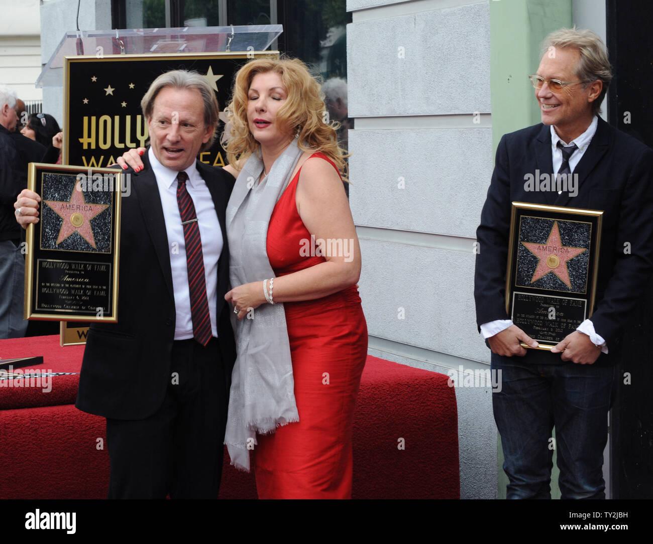"""Dewey Bunnell (L) y Gerry Beckley (R), miembros del grupo de rock clásico y ganador de un premio Grammy, """"el dúo América, sujetar placas de réplica después de que fueron honrados con el 2,459th estrella en el Paseo de la Fama de Hollywood durante una ceremonia en Los Angeles el 6 de febrero de 2012. Bunnell es retratada con su esposa Penny. UPI/Jim Ruymen Imagen De Stock"""