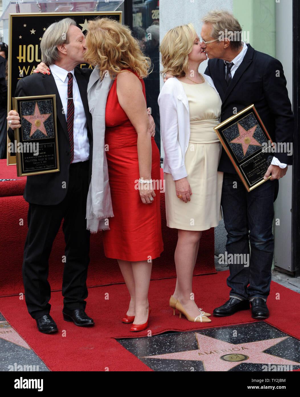 """Dewey Bunnell (L) y Gerry Beckley (R), miembros del grupo de rock clásico y ganador de un premio Grammy, """"el dúo América, sujetar placas de réplica después de que fueron honrados con el 2,459th estrella en el Paseo de la Fama de Hollywood durante una ceremonia en Los Angeles el 6 de febrero de 2012. Bunnell y Beckley se muestren con sus esposas Penny (2nd-L) y Kathy (3RD-L). UPI/Jim Ruymen Imagen De Stock"""
