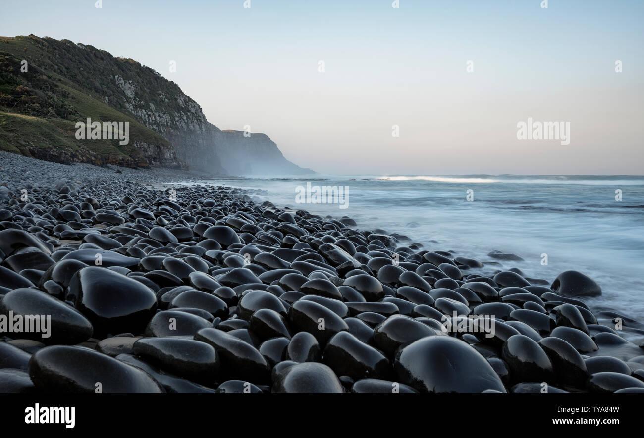 La increíble playa de guijarros negros de arcilla blanca, con reminiscencias de una época de invierno pelágicos andanzas e historias marineras. Café Bahía, Eastern Cape Foto de stock