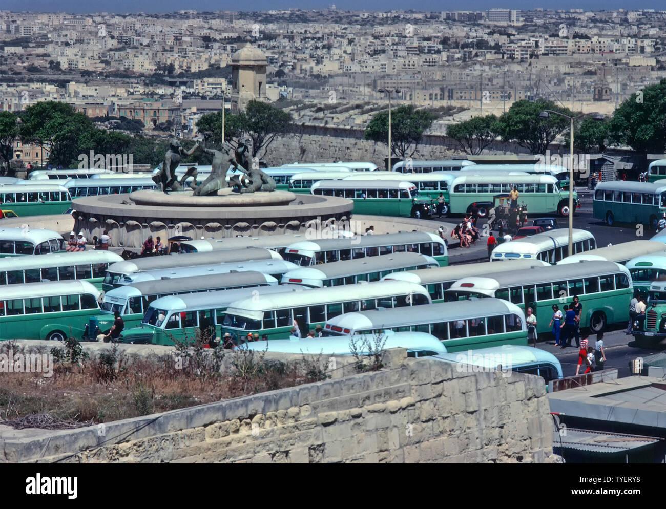 Imagen de archivo histórico estación principal de autobuses de la Valeta autobuses pintados de verde 1975 - 1995 estacionada alrededor muy alterados tres tritones estatuas de bronce de Malta Imagen De Stock