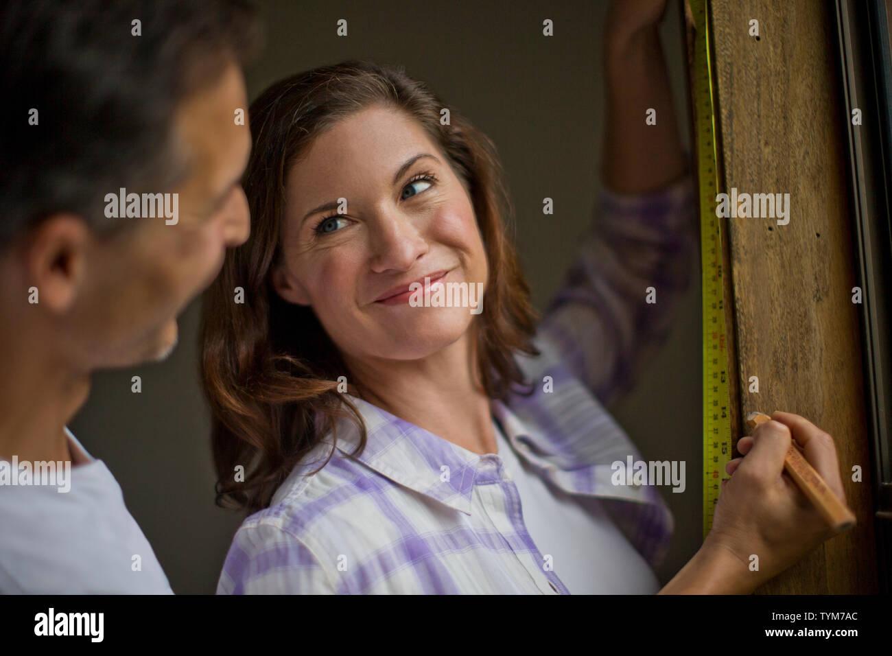 Mujer joven toma un descanso en el alféizar de la ventana de medición para sonreír amorosamente a su guapo marido, quien acaba de llegar hasta detrás de ella. Imagen De Stock