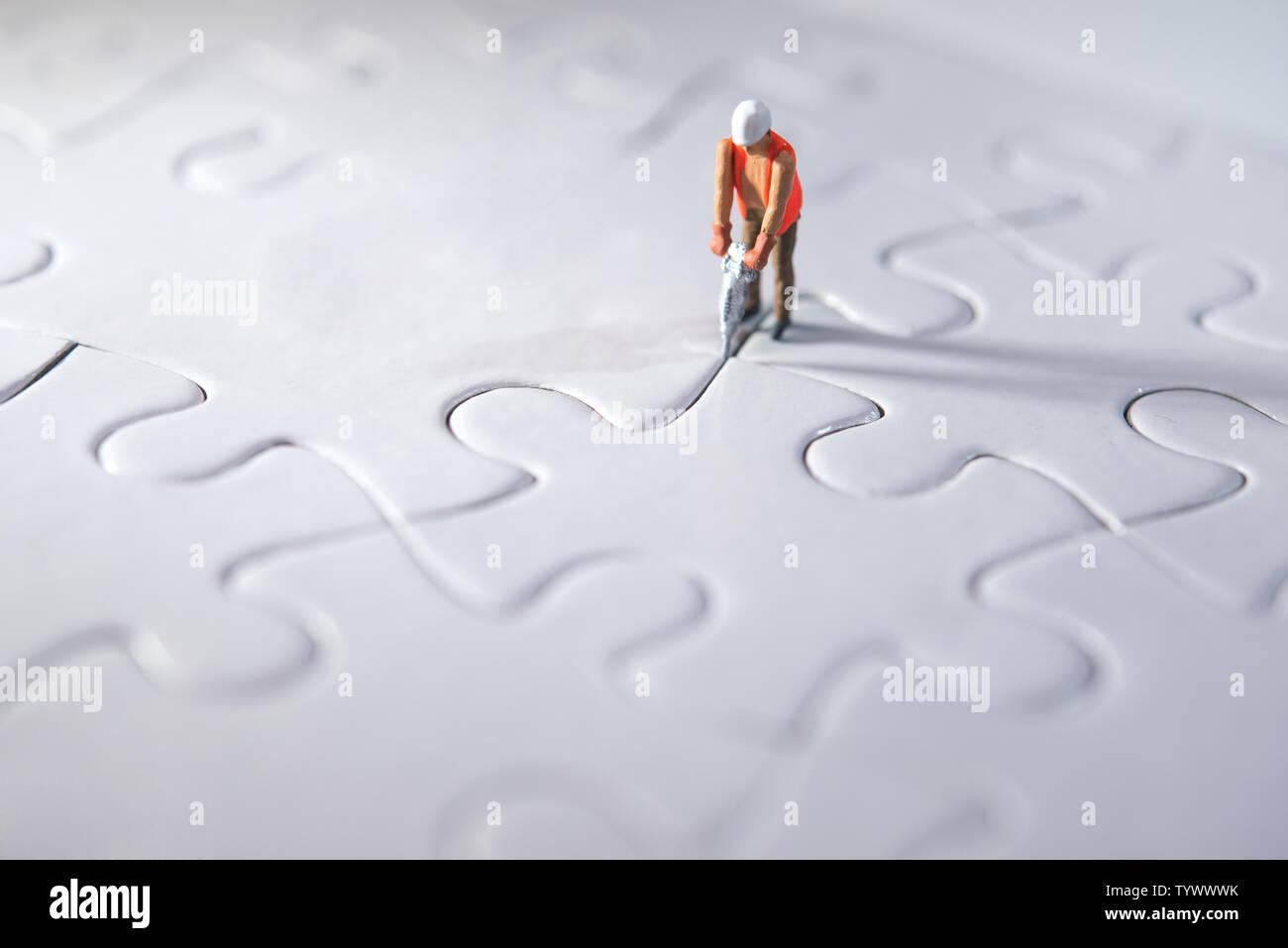 Persona en miniatura Construcción puzzles, haciendo camino para el equipo y el concepto de trabajo. Concepto de esfuerzo Foto de stock