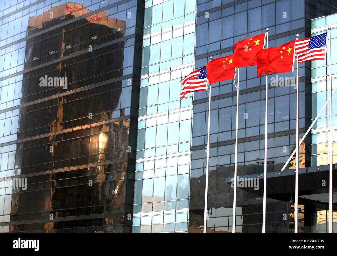 """Tanto las banderas nacionales estadounidenses y chinos vuelan delante de un nuevo centro de finanzas internacional en el centro de la ciudad de Beijing el 23 de noviembre de 2011. Los Estados Unidos esta semana celebró conversaciones comerciales clave con China como un éxito, diciendo que había hecho 'meaningful, progresos concretos"""" sobre la piratería y el acceso a los mercados, pero se les advirtió que era necesario trabajar más. UPI/Stephen afeitadora Foto de stock"""