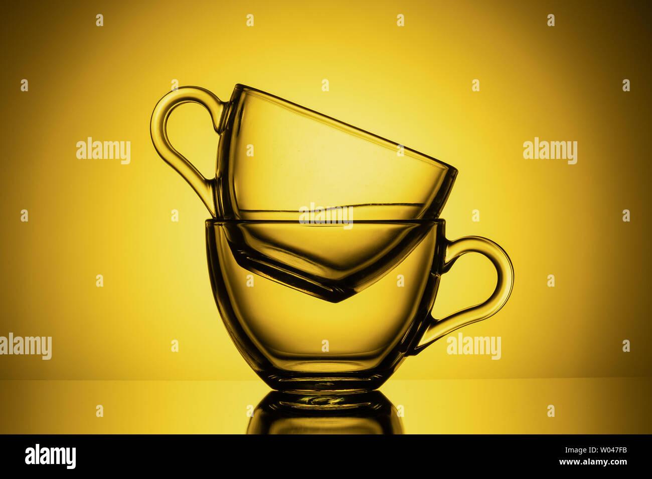 Dos tazas de cristal transparente para el té. Fondo amarillo, close-up, diseño horizontal Foto de stock