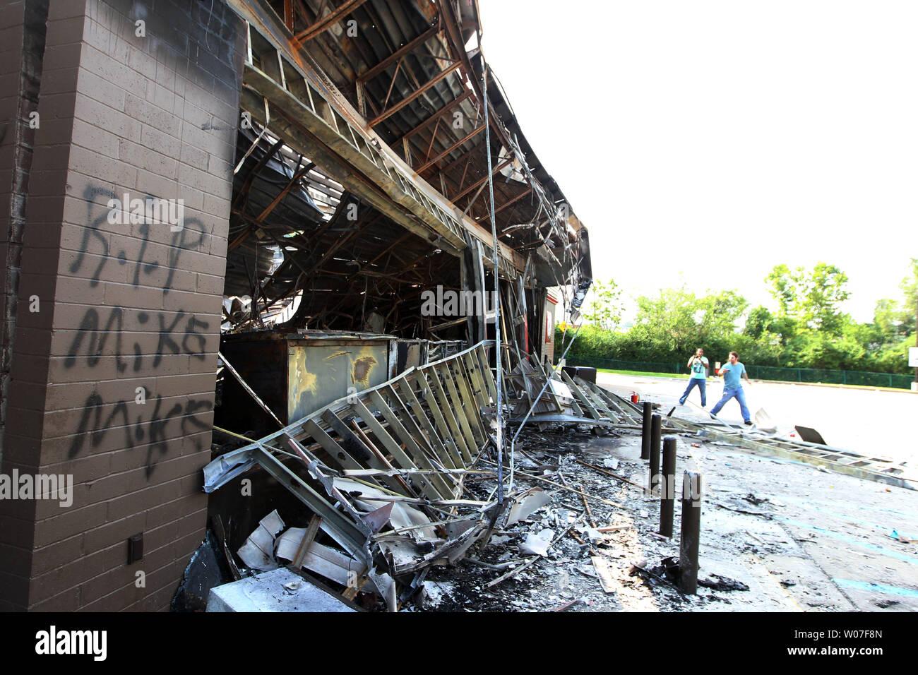 Los visitantes obtener una mirada más cercana a una gasolinera QuikTrip tras una noche de disturbios, saqueos e incendios provocados en Ferguson, Missouri, el 11 de agosto de 2014. La gente está enojada a causa de los disparos de la policía de Ferguson y la muerte de un adolescente negro desarmado Michael Brown, el 9 de agosto de 2014. En todos los alrededor de 20 empresas sufrieron daños tras una vigilia con velas se tornaron violentas. UPI/Bill Greenblatt Foto de stock