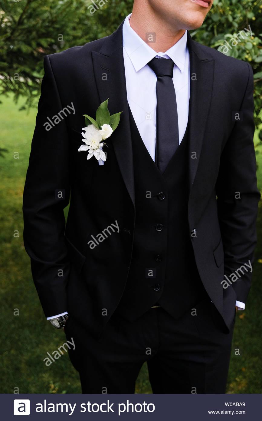 El novio en una camisa blanca, corbata, traje azul oscuro o