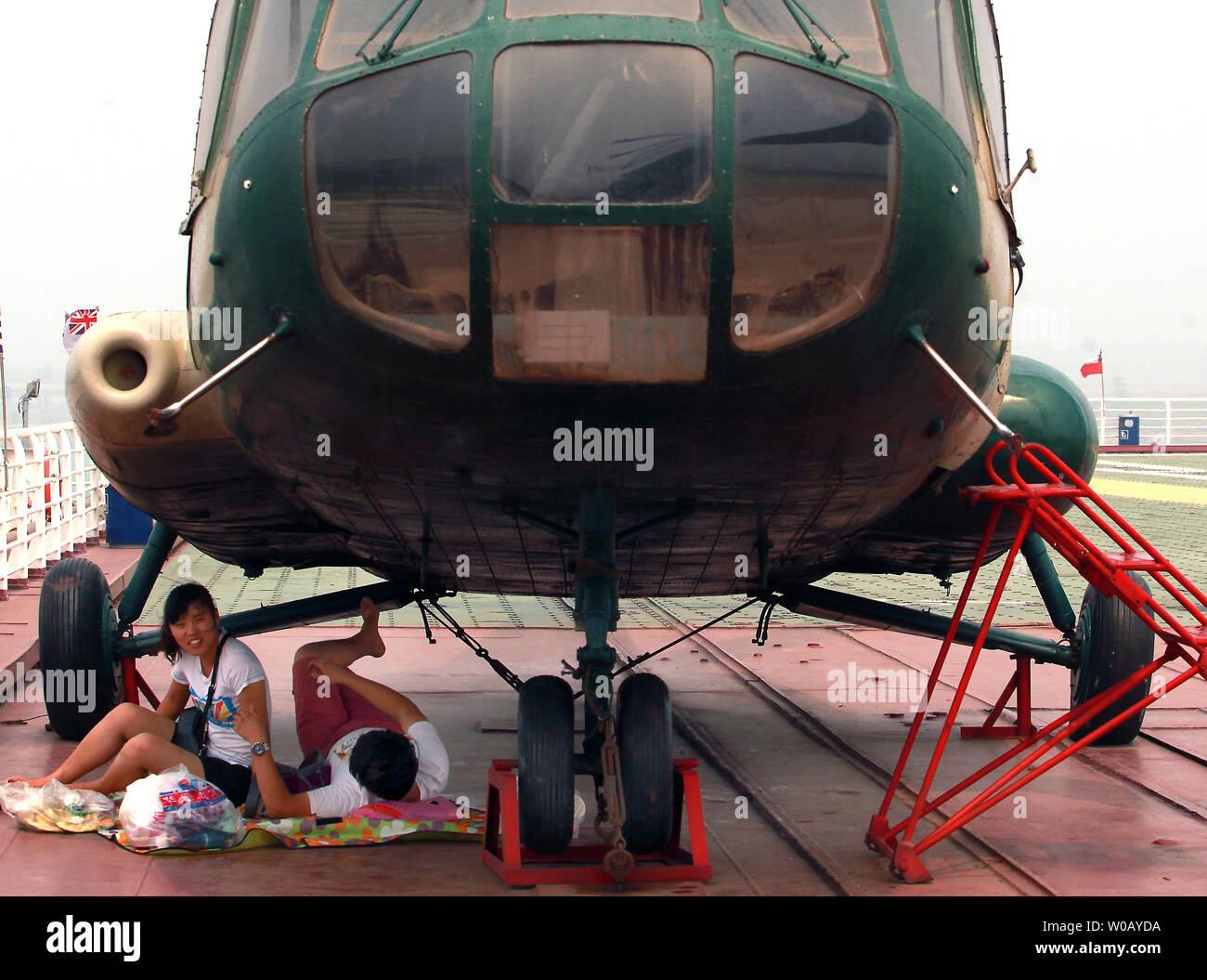 Los turistas chinos visitar el portaaviones Binhai Theme Park, con el ex-Federación de aviones pesados cruiser el Kiev, en Tianjin el 29 de julio de 2014. La Kiev era un avión pesado de transporte de crucero que sirvió a la armada rusa y soviética de 1975 a 1993 antes de ser vendida a una empresa china en 1996 para uso militar en un parque temático. Más de 15,5 millones de dólares se dedicó a la restauración y equipamiento de la ex-buque de guerra en un hotel de lujo desarrollado por el turismo y la atracción de ocio consultor Quest International (EE.UU.). UPI/Stephen afeitadora Foto de stock