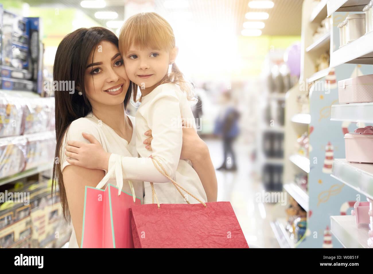 cd70ee75d2b Vista frontal de la alegre morena mantener niños en manos y juntos de  compras en la