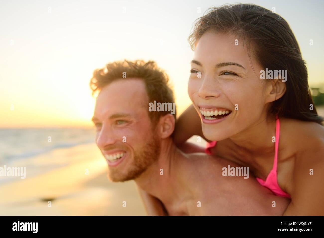 Playa par riendo en amor divirtiéndose romance de luna de miel viajes vacaciones vacaciones de verano. Los jóvenes personas felices, Asiáticos y Caucásicos mujer hombre abrazando al aire libre en la playa tropical de ropa casual. Foto de stock