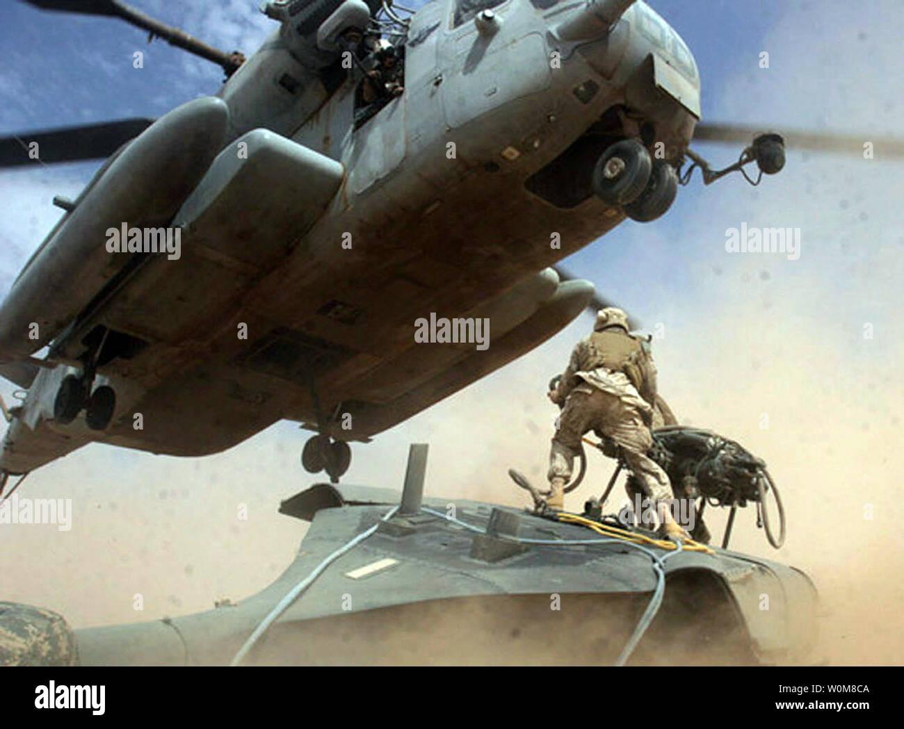 Los infantes de Marina de EE.UU. compañía de logística de combate 117, luchar contra el batallón logístico 7, plataformas una cuerda desde un helicóptero Black Hawk UH-60 a un tipo CH-53E Super Stallion de helicópteros para carga pesada en Al Asad, Irak el 18 de marzo de 2006. (UPI foto/Corp. William Dubose/DOD) Imagen De Stock