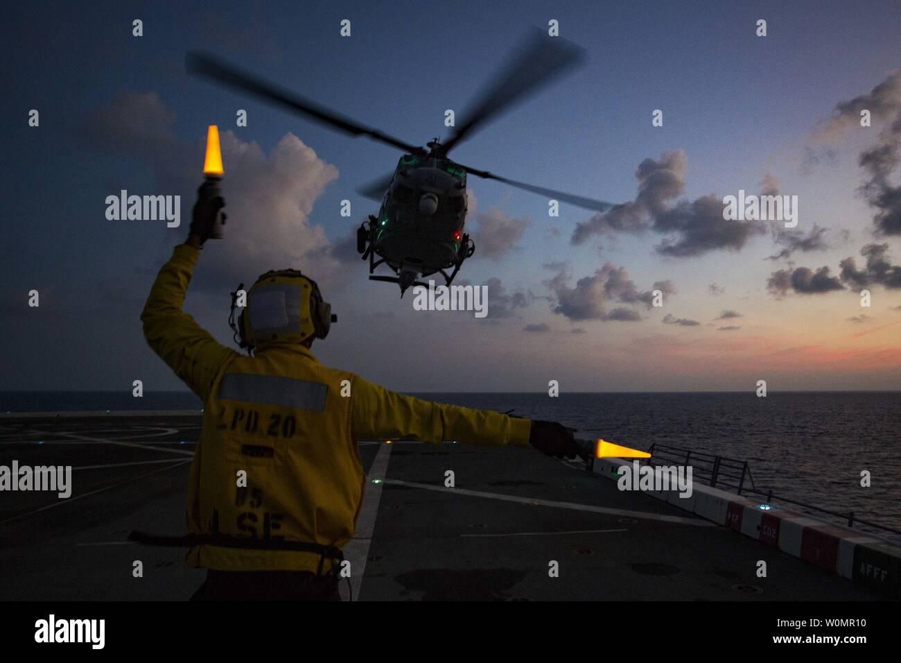"""Petty oficial de 2ª clase Torien Collins, un compañero boatswainÕs aviación, dirige un Marine Corps UH-1Y Venom """"Huey"""" helicóptero desde medio marino Tiltrotor Escuadrón 262 (reforzado), 31ª Unidad Expedicionaria de los Infantes de Marina, para despegar desde la cubierta de vuelo del USS Green Bay (LPD-20), en el mar, el 23 de agosto de 2016. Foto por J. Darien Bjorndal/U.S. Marine Corps/UPI Foto de stock"""
