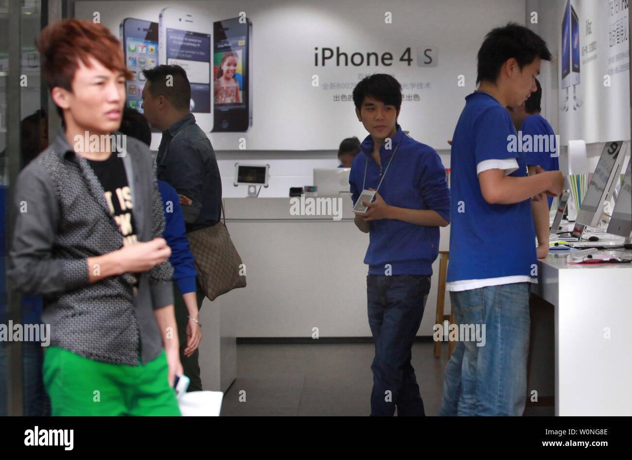 """Los empleados chinos vestidos como oficiales de Apple en una tienda de informática personal exaltando a sí mismo como un """"oficial"""" de Apple store ayuda a los clientes a comprar productos Apple en Kunming, la capital de la provincia de Yunnan, el 21 de septiembre de 2012. Kunming ha tenido varios 'Apple' almacena cese y desista de hacer las flagrantes infracciones de copyright y marcas comerciales. UPI/Stephen afeitadora Foto de stock"""
