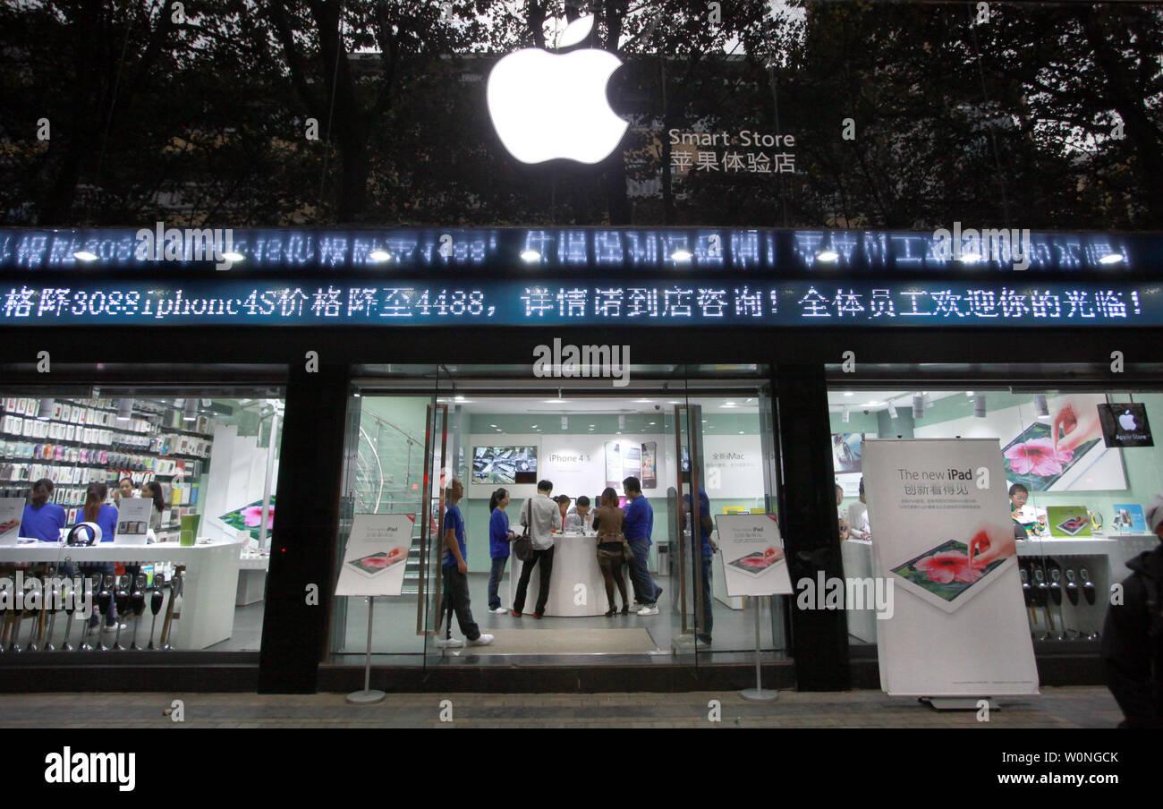 """Los empleados chinos vestidos como oficiales de Apple al personal a trabajar en una tienda de informática que pregonaba flagrantemente a sí mismo como un oficial """"inteligente Apple Store, los clientes de venta real y 'Gris' los productos de Apple en Kunming, la capital de la provincia de Yunnan, el 24 de septiembre de 2012. Kunming tiene varias tiendas 'Apple' el año pasado de cesar y desistir a despreciar abiertamente las infracciones de copyright y marcas comerciales. En el caso de stands, muchas veces una demostración de fuerza por parte del gobierno para atacar y resolver esos problemas suele ser sólo temporal con el fin de apaciguar a los reclamantes. UPI/Stephen afeitadora Foto de stock"""