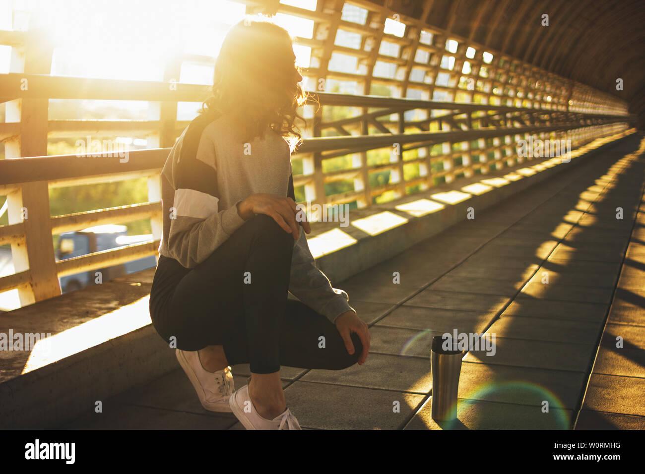Esbelta joven morenita mujer bailarina callejera gimnasta sentarse y descansar con termo taza en la calle puente al amanecer Foto de stock