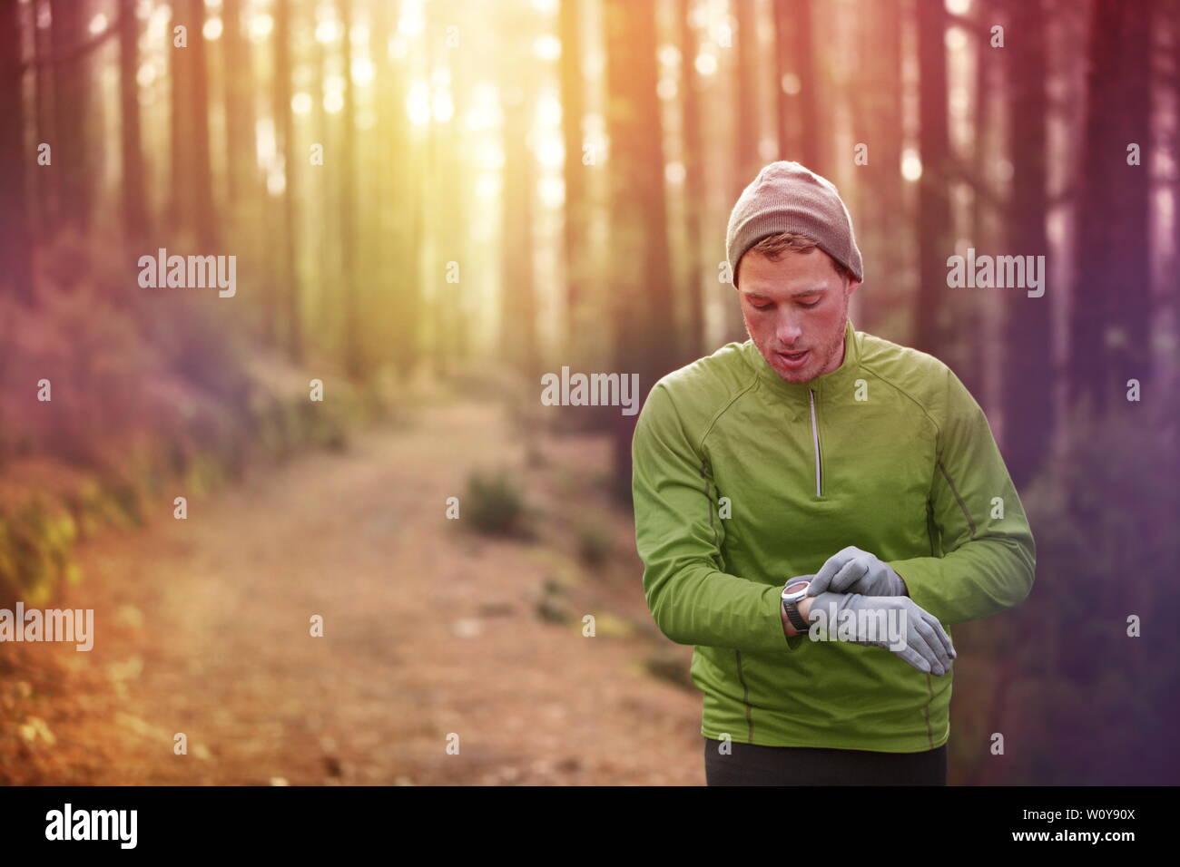 Trail running runner mirando al monitor de ritmo cardíaco ver corriendo en el bosque vistiendo chaqueta deportiva, gorro y guantes. Emparejador macho ejecuta la formación de bosques. Foto de stock