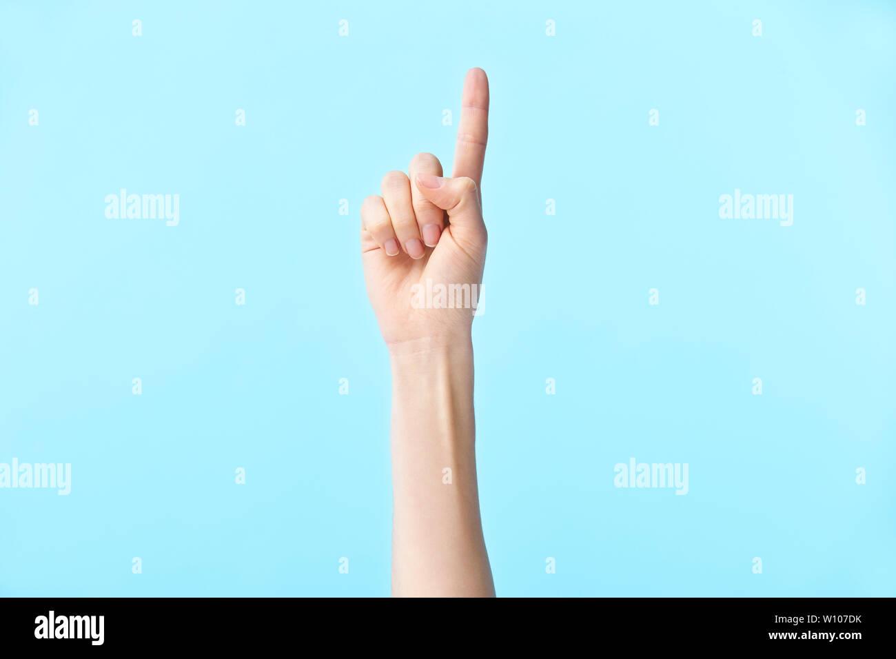 La mano humana mostrando número uno, aislado sobre fondo azul. Imagen De Stock