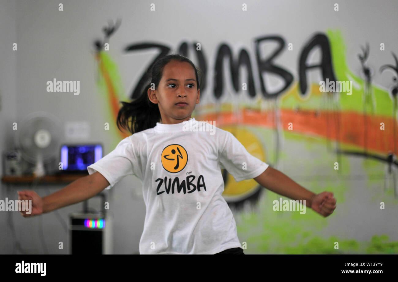 """La ciudad de Gaza, FRANJA DE GAZA, Territorio Palestino. El 30 de junio, 2019. Los niños palestinos participan en una clase de Zumba durante las vacaciones de verano, al Jalaa Gym, en la ciudad de Gaza, el 30 de junio de 2019. Zumba es un ejercicio programa fitness creado por el bailarín y coreógrafo colombiano Alberto """"Beto"""" Pérez durante el decenio de 1990. Crédito: Mahmoud Ajjour APA/Images/Zuma alambre/Alamy Live News Imagen De Stock"""