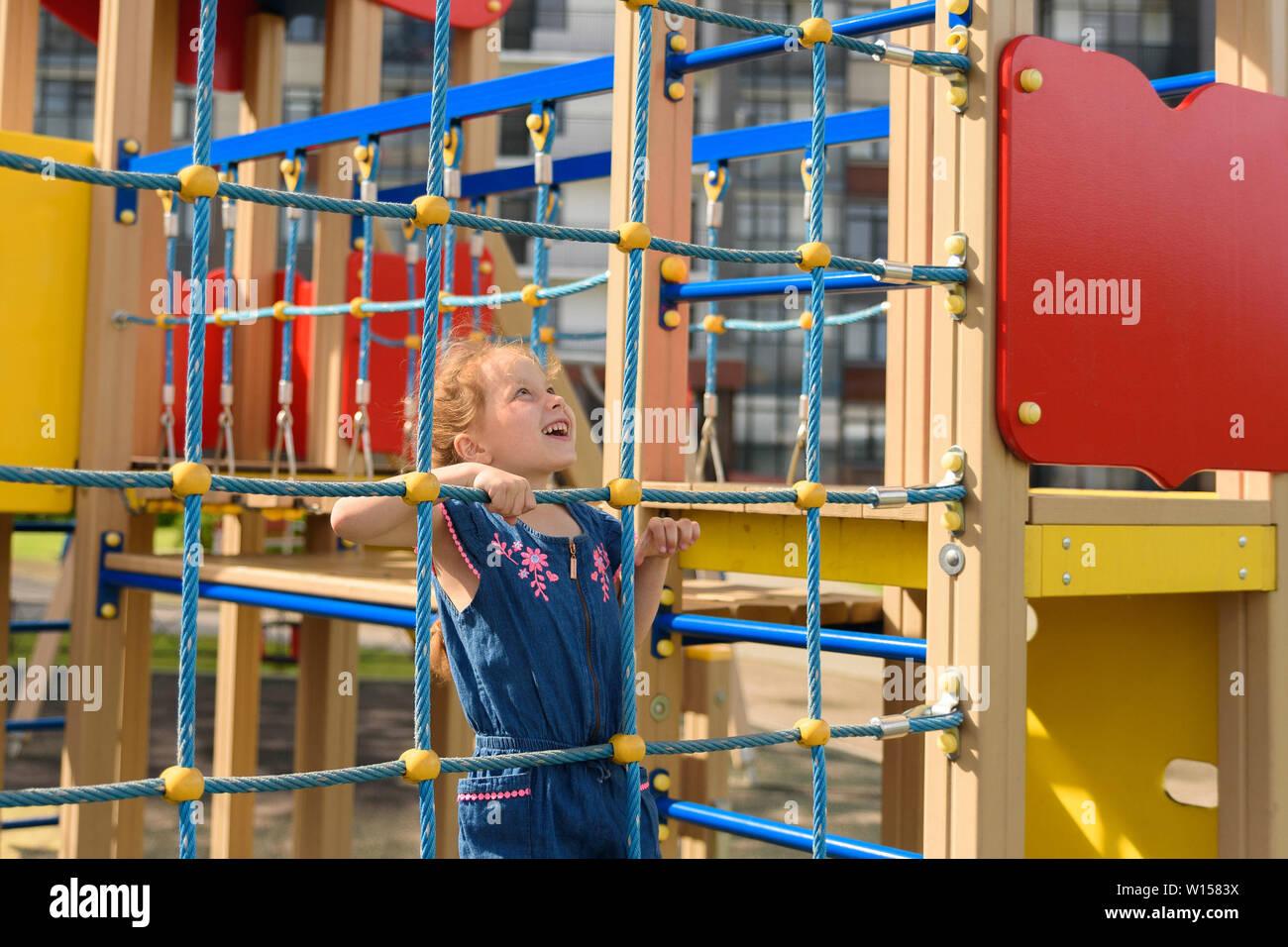 Adolescente intenta subir en la cuerda de la pared. Ella está jugando con la cuerda de pared para desarrollar la actividad motora en el parque Foto de stock