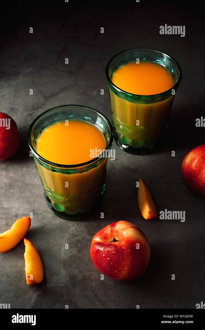 Still life de frescas deliciosas nectarinas con gotitas de agua y zumo de gafas vintage turquesa sobre fondo oscuro. Bajo llave. Foto de stock
