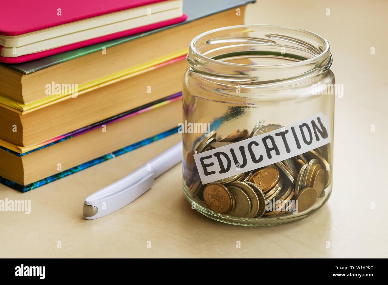 Frasco de vidrio con un montón de monedas y educación palabra cerca de white bolígrafo y algunos libros sobre una mesa. Ahorro de dinero por concepto de educación. La planificación. Foto de stock
