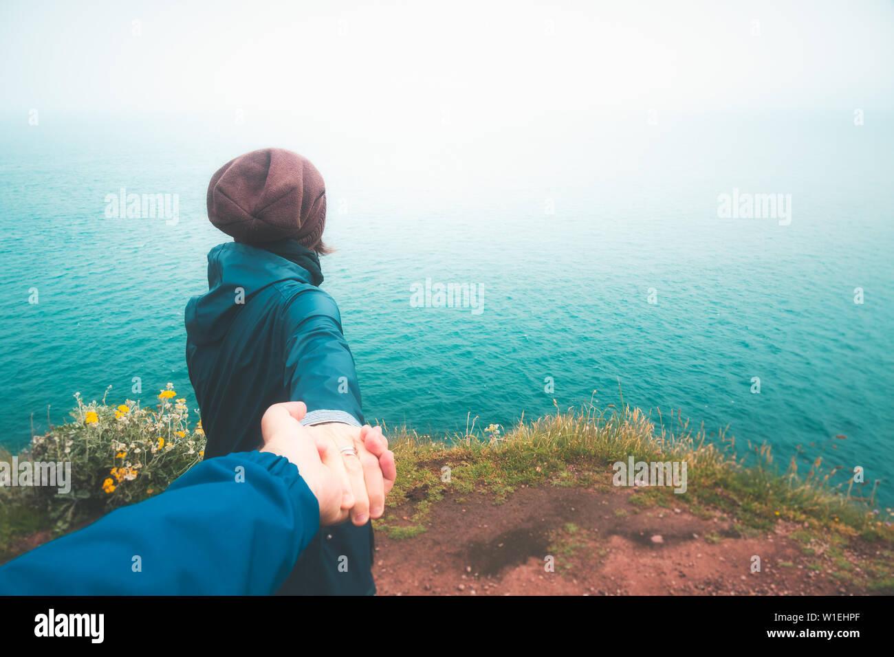 Sígueme. Chica tomando la mano de su novio caminando hacia el borde del acantilado con vistas al mar en un día lluvioso y temperamental. Concepto de viaje al aire libre Foto de stock