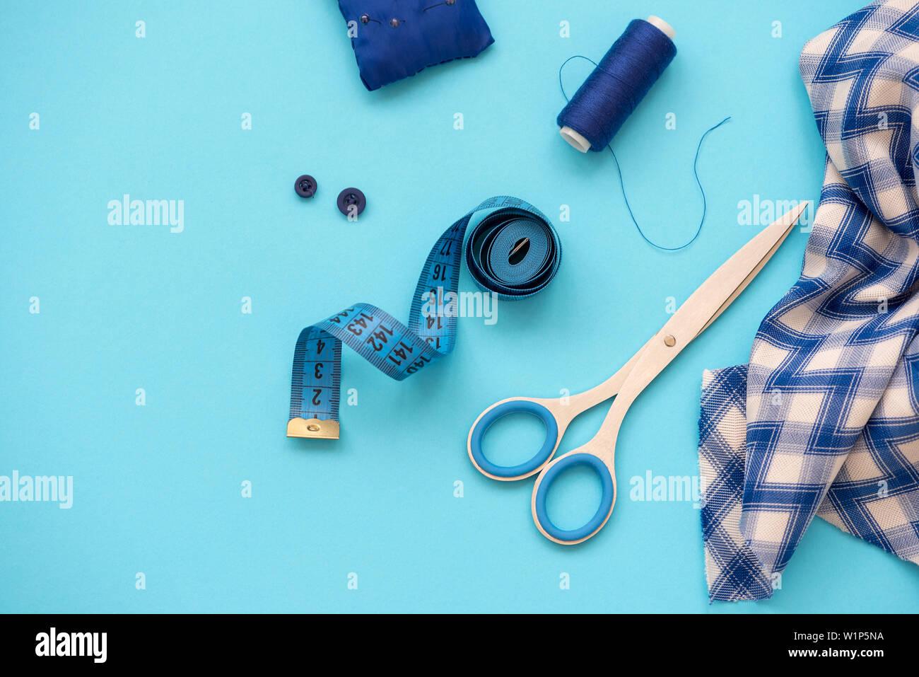 Accesorios de costura con hilos, tijeras, alfileres, tela, botones y cintas de coser sobre fondo azul. Vista desde arriba. Sentar planas. Foto de stock