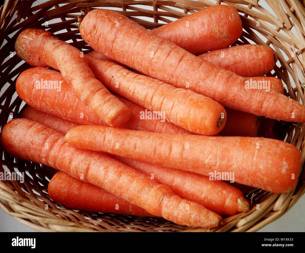 Las zanahorias con color brillante en una canasta, ingredientes saludables en la cocina Foto de stock