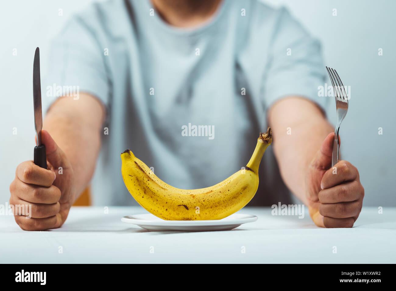 Hombre sentado detrás de una mesa con un tenedor y un cuchillo en la mano y un plátano fresco sobre una placa en una tabla blanca , la hora de comer - Alimentación saludable concepto Foto de stock