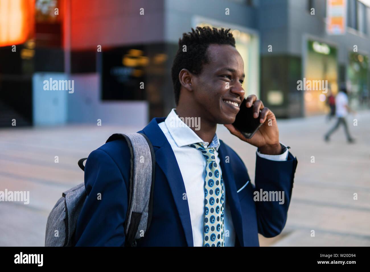 Empresario afroamericano holding móvil vistiendo traje azul Foto de stock