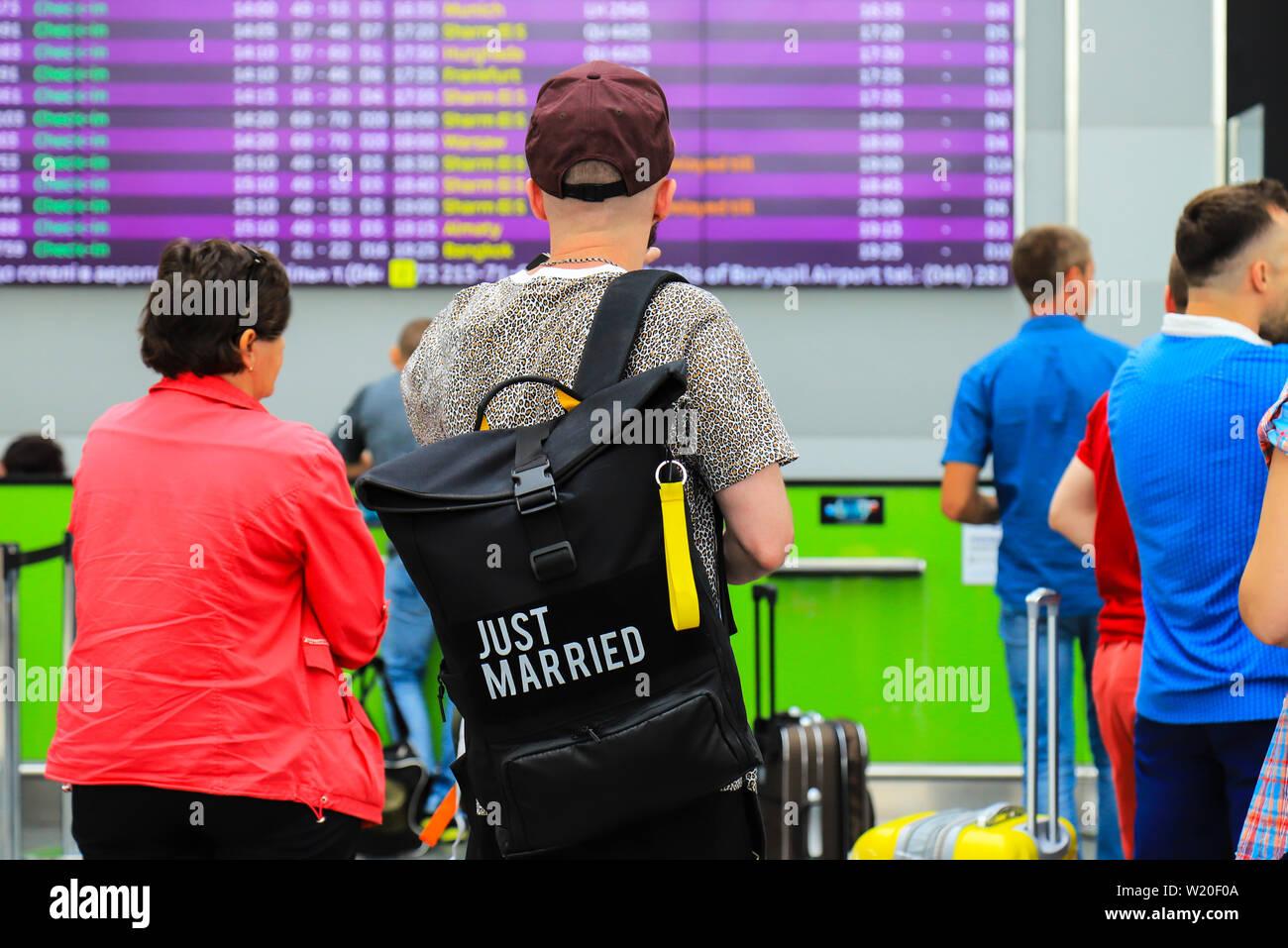 Un hombre joven con una bolsa negra con la inscripción - recién casada está de pie cerca de un tablero de información acerca de la fecha de llegada y de salida en el aeropuerto. Imagen De Stock