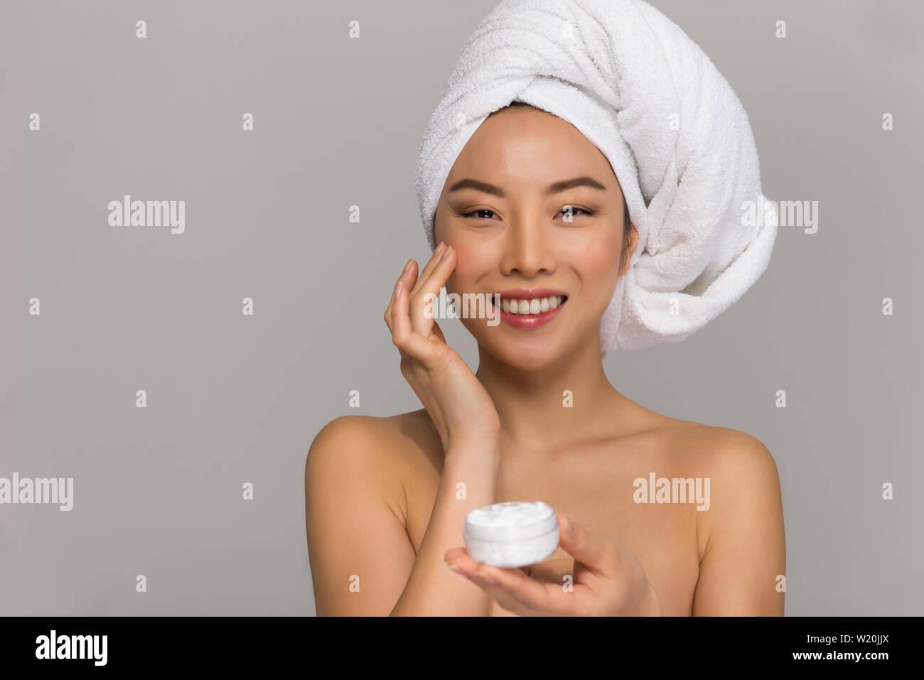 Hermosa mujer asiática retratos de belleza. Niña china de pie frente al espejo y teniendo cuidado de su mirar fotografías de estudio de belleza. Foto de stock