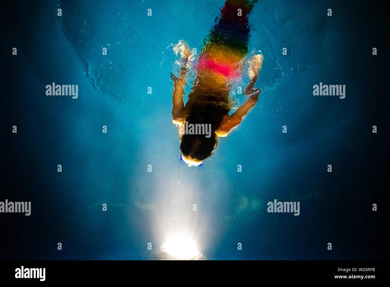 Buceo de sirena hacia la luz de una piscina azul en la noche, con un fondo de ensueño de la fantasía y la imaginación. Foto de stock