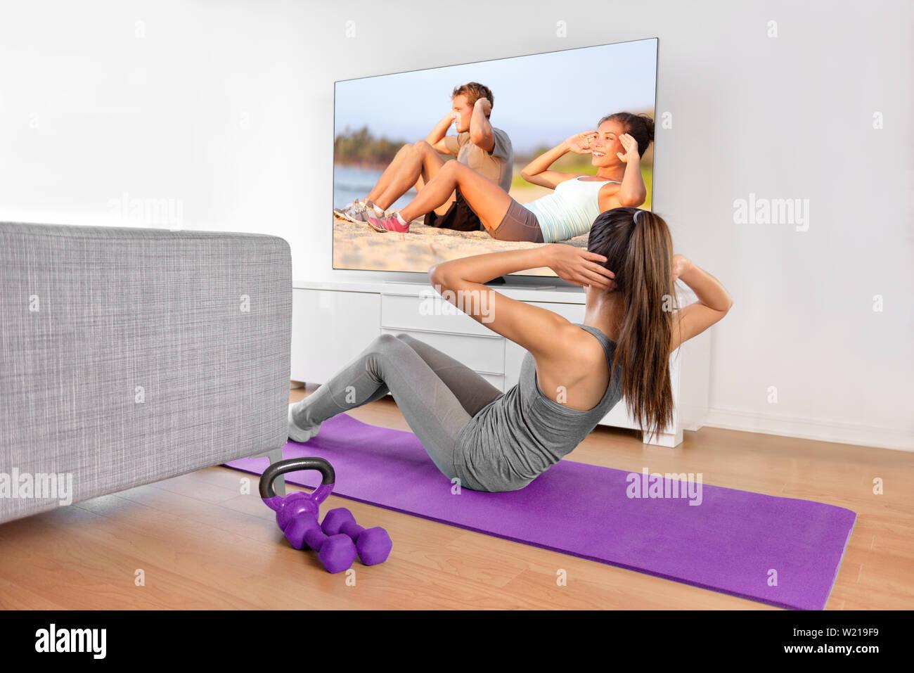 Inicio del entrenamiento - mujer ejercicio delante de una pantalla plana mirando un programa de fitness o ejercicio durante un programa de televisión acostado sobre una estera del yoga en frente del sofá en el salón de una casa o apartamento. Imagen De Stock