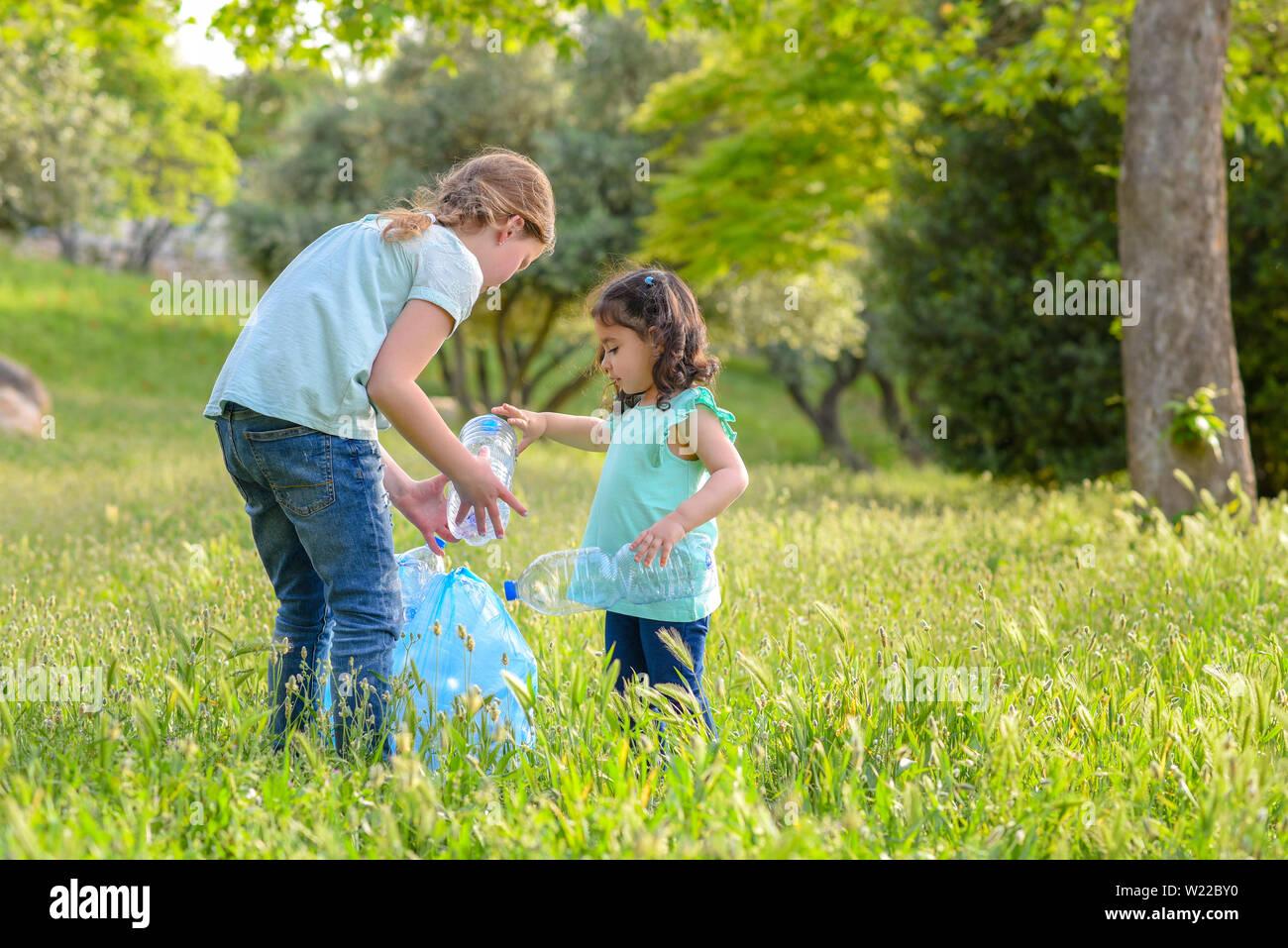 Contaminación plástica en tierra. Cildren recogiendo una botella plástica de hierba en el Parque contaminado. Foto de stock