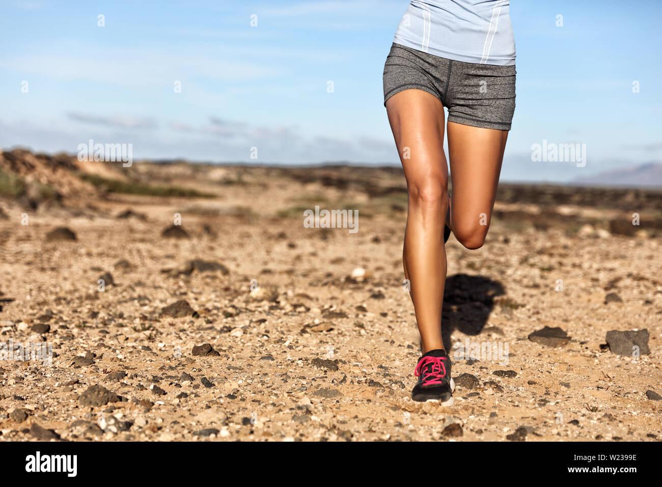 Verano atleta trail runner piernas cuerpo inferior de cosecha. Mujer Fitness trotar viviendo un estilo de vida activo trotar en camino rocoso en la naturaleza del paisaje de montaña. Zapatos, rodillas, muslos, concepto de pérdida de peso. Foto de stock