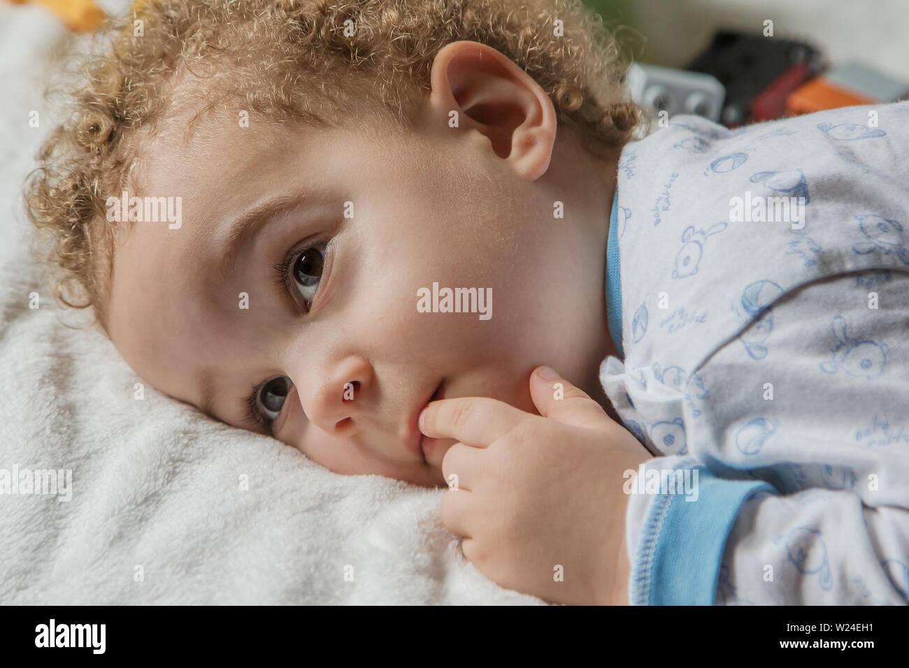 Adorable dos años cabrito en pijama suave con colores azul y cone en la soleada habitación de los niños. El sueño del niño concepto, enfoque suave. Foto de stock
