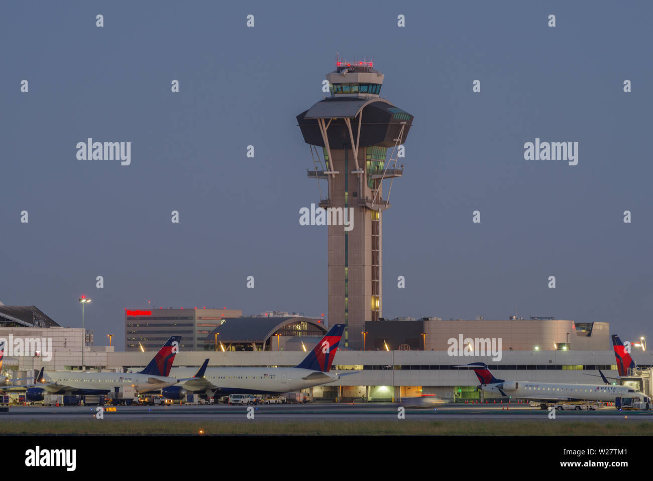 Imagen de la torre de control y Delta Air Lines chorros en la puerta en el Aeropuerto Internacional de Los Angeles, LAX, al anochecer. Foto de stock