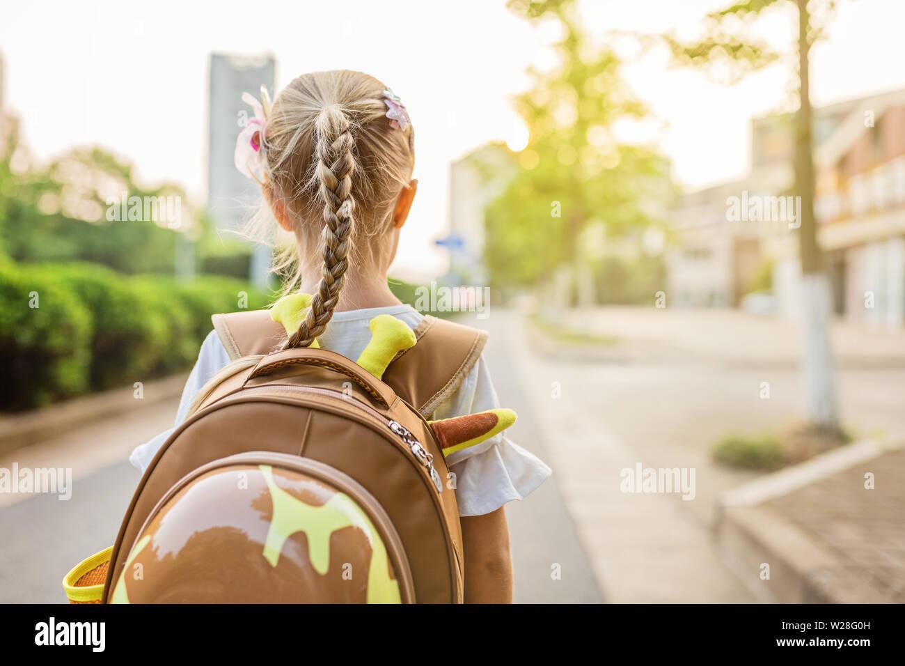 Kid alumna desde detrás caminando de regreso a casa después de la escuela de estudio de aprendizaje solo con mochilas escolares y preescolares, el kindergarten el concepto de educación. Primera Foto de stock